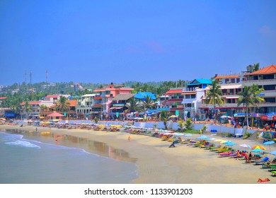 Kovalam, India - March 06, 2018: Tourists relaxing by the crescent shaped sea beach.