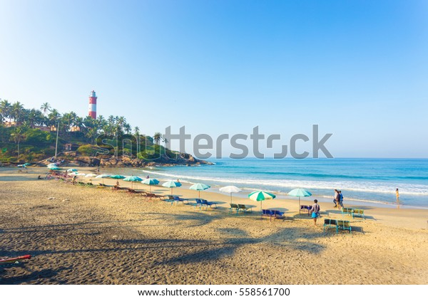 Kovalam, India - March 1, 2015: Beach chairs and parasols line the beachfront on the sand in view of ocean waves at Kovalam Light House Beach in Kerala