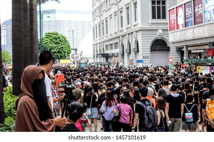 Kowloon, China July 7, 2019 - Muslim woman watching the Anti-Extradition Protests along Nathans Road Tsim Tsa Tsui
