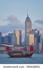KOWLOON, HONG KONG - MAY 2016: Evening view from Kowloon over the harbor to a traditional Chinese junk with red sails and the Hong Kong skyline in the background.