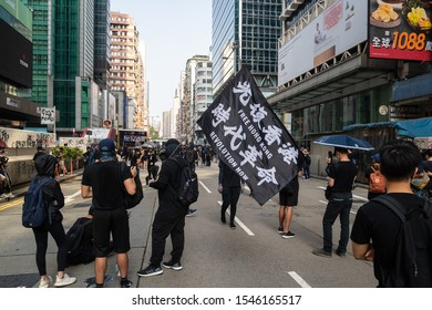 Kowloon, Hong Kong - October 20 2019: Masked protestor hold a Free Hong Kong Revolution Now black flag during a protest against the governement in Mong Kong in Hong Kong SAR
