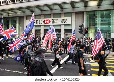 Kowloon, Hong Kong - October 20 2019: Masked protestors wave American and British flags during a protest against the governement in Mong Kong in Hong Kong SAR