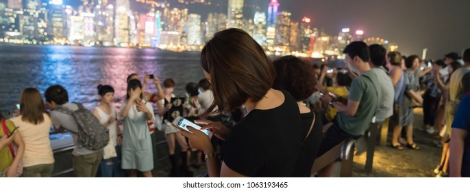 KOWLOON HONG KONG, SEPTEMBER 20; Tourists gather along Walk of Stars to view and take selfie of Victoria Harbor and commercial skyline at night September 20 2017, Hong Kong