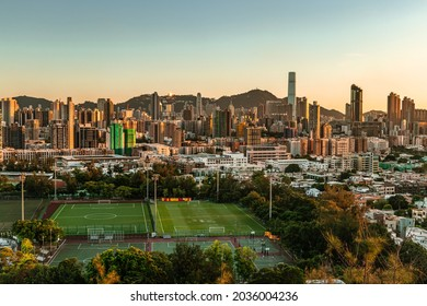 Kowloon, Hong Kong - September 3, 21: A panoramic view of cityscape of Kowloon and Hong Kong Island from Checkerboard Hill. Architectures and football fields were plated with gold by the sunset.