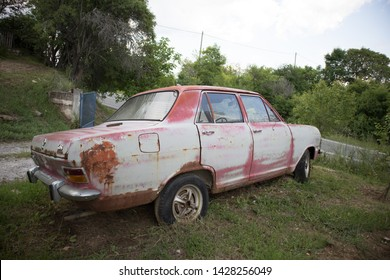 Kozani, Greece - June 2019: An abandoned antique Opel car, with faded red color.