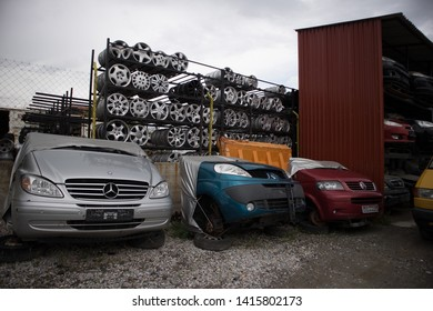 Kozani, Greece - May 2019: A car graveyard, with the front part of half cut vehicles that awaiting dismantling or recycling. Also, automobile rims for sale.