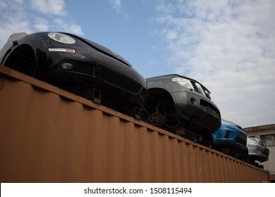 Kozani, Greece - May 2019: The front part of four half cut cars without wheels. On the upper side of a shipping container. At a car graveyard. Awaiting dismantling, recycling or re-sale.