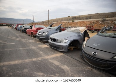 Kozani, Greece - October 2019: Half cut or complete cars in a line, during the dusk. At a car cemetery. Awaiting dismantling, recycle or re-sale.