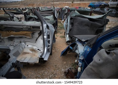 Kozani, Greece - October 2019: Only the front part from half cut cars. Awaiting dismantling or recycle. More automobiles in background.