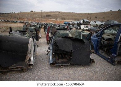 Kozani, Greece - October 2019: Only the front part from half cut cars. Awaiting dismantling or recycle. More automobiles appear in background.