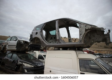 Kozani, Greece - October 2019:Damaged cars one on top of each other, with missing engines, bonnets, doors, axles, wheels or other parts. Awaiting dismantling, re-sale or recycling. At a car graveyard.