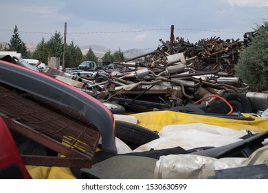 Kozani, Greece - September 2019: Car bumpers, used rims, rusty vehicle exhausts and other parts, stacked in an unarranged order. Awaiting dismantling, recycling or re-sale. At a car graveyard.