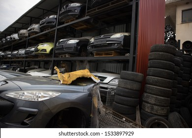 Kozani, Greece - September 2019: A car graveyard, with the front part of vehicles to awaiting dismantling, recycle or resale. Used tires and rims on the right.