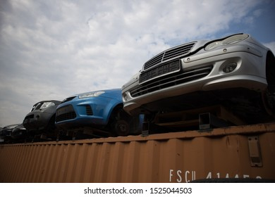 Kozani, Greece - September 2019: The front part of half cut cars without wheels. On the upper side of a shipping container. At a vehicle graveyard. Awaiting dismantling, recycling or re-sale.
