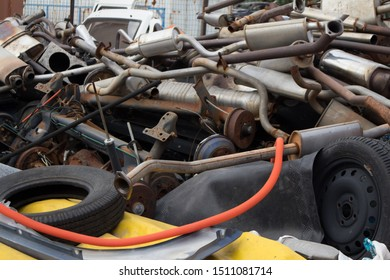 Kozani, Greece - September 2019: Rusty vehicle exhausts,  axles, used tires and other parts, stacked in an unarranged order. Awaiting dismantling, recycling or re-sale. At a car cemetery.