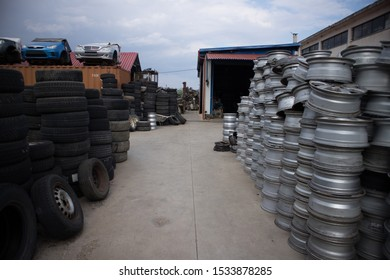 Kozani,Greece-September 2019: Used tires and old rims for resale. Half part of three cars without wheels, on the upper side of a shipping container, in background. At a vehicle cemetery.