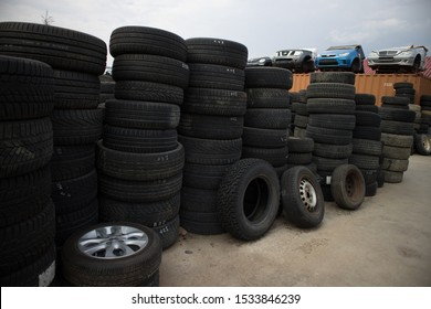 Kozani,Greece-September 2019: Used tires for resale. In background, half part of four cars without wheels, on the upper side of a shipping container. At a car cemetery.