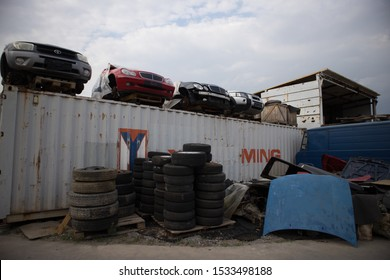 Kozani,Greece-September 2019:Front part of four half cut cars without wheels. On the upper side of a shipping container. Used tires and other parts in front. At a car cemetery.Awaiting recycle or sale