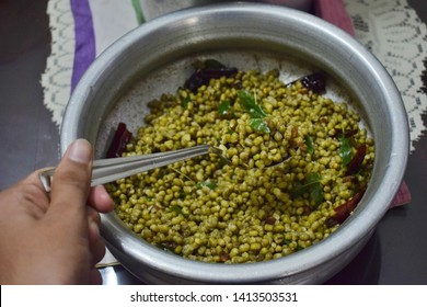kozhikode,kerala,06-02-2019. A young boy holding green gram in a spoon on a background with a large amount of green gram in a bowl.