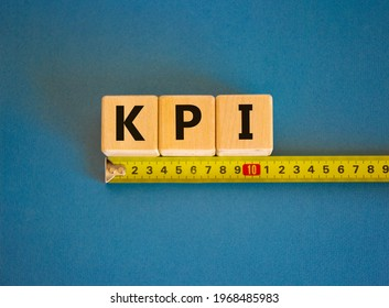 KPI - key perfomance indicator symbol. The word KPI, key perfomance indicator on cubes arranged behind the ruler on beautiful blue background. Copy space. Business and KPI level concept.