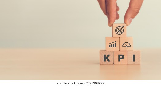 KPI, Key Performance Indicator. Businessman holds cube with KPI icon; business goals, performance results and indicators . For business planning and measure success, target achievement. Copy space.