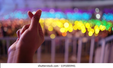 K-Pop music or Live concert theme with female hand making mini heart shaped hand gesture for artist supporting on blurred background of audience in a hall with rainbow colors bokeh defocused lights.