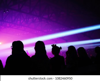 K-Pop music theme or live concert silhouette of girls or diverse audience in large music hall with followspot and stage lighting. Enjoy Music and Entertainment Concept. (Space for text/article layout)