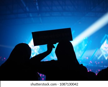 K-Pop music theme or live concert background silhouette of Muslim girls or audience holding a sign for artist supporting in large music hall with beautiful stage lighting. Enjoy Music Concept.