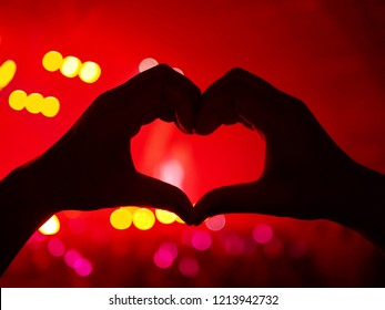 K-Pop music theme or Live concert background with silhouette hands of audience making heart shaped hand gesture for artist supporting on blurred red background of a large stage with bokeh light.