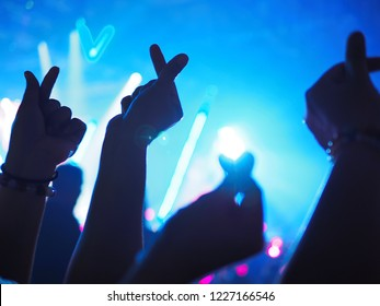 K-Pop music theme or Live concert background with silhouette hands of audience making mini heart shaped hand gesture for artist supporting on blurred background of audience and stage with neon light.