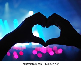 K-Pop music theme or Live concert background with silhouette hands of audience making heart shaped hand gesture for artist supporting on blurred background of a large stage with bokeh defocused lights