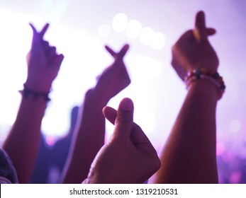 K-Pop music theme or Live concert background with hands of audience making mini heart shaped hand gesture for artist supporting on blurred background of audience and stage with lighting effects.