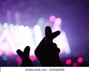 K-Pop music theme or Live concert background with silhouette hands of audience making mini heart shaped hand gesture for artist supporting on blurred background of stage with lighting effects.