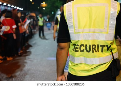 K-Pop music theme security guard with blurred crowd of audience or diversity people at concert venue entrance. Enjoy Music and Entertainment Concept. (selective focus, space for text, article layout)