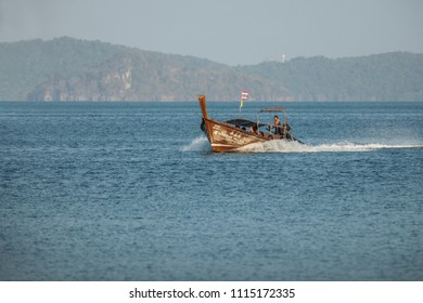 KRABI, THAILAND - CIRCA MAR 2013: Andaman sea. Tourists riding on a traditional Thai boat