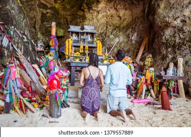 Krabi, Thailand - February 12. 2019: Couple, man and woman pray fertility goddess for pregnancy in front of the phallus shaped figurines of the Phra Nang Princess Cave.