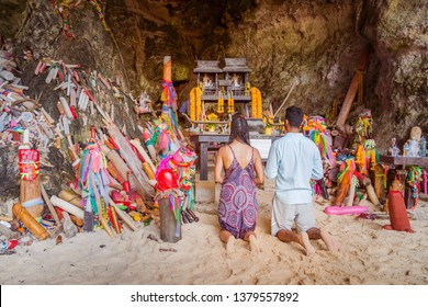 Krabi, Thailand - February 12. 2019: Couple, girl and boy pray fertility goddess for pregnancy in front of the phallus shaped figurines of the Phra Nang Princess Cave.