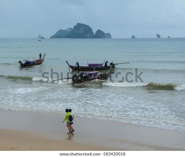 Krabi, Thailand - Jun 21, 2016. Long-tail boats waiting on Ao Nang beach in Krabi, southern Thailand. Kayaking, sailing, snorkeling are also among top activities in Krabi.
