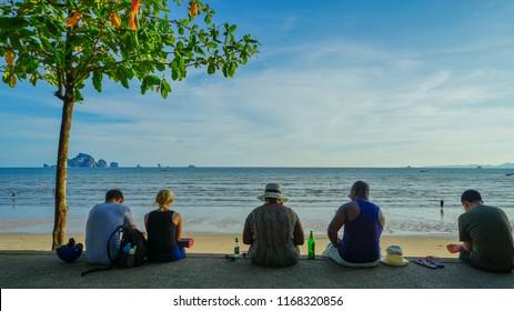 Krabi, Thailand - May 15th 2018: People enjoying the sunset on Ao Nang beach.