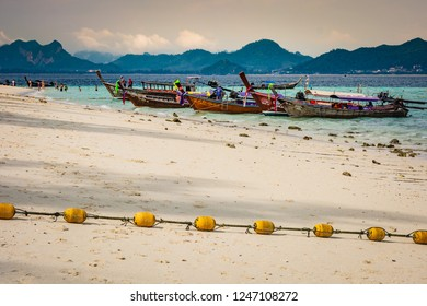 KRABI, THAILAND - NOVEMBER 2018: Beach on the island near Krabi, wooden boats and yellow buoys on the beach, the mountainous part of the island in the background