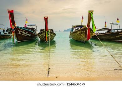 KRABI, THAILAND - NOVEMBER 2018: Thai traditional wooden boats with ribbon decoration at ocean shore near Krabi, Thailand