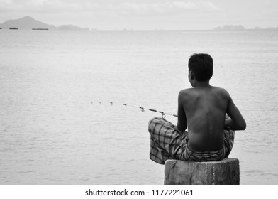 KRABI, THAILAND - OCTOBER 10, 2010: Young asian boy with no shirt sitting on top of concrete pillar in the sea for fishing, black and white tone