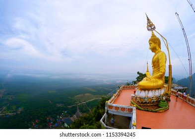 Krabi, Thailand, October 23, 2014: Golden Buddha statue at the top of the Wat Tham Sua with the Krabi coastline in the background.