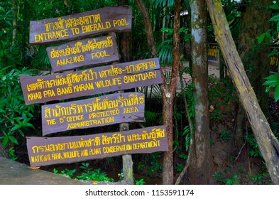 Krabi, Thailand - October 23, 2014: Wooden information signs at the entrance of the area of Sa Morakot, or Emerald Pool.