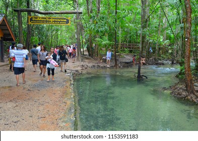 Krabi, Thailand - October 23, 2014: People walking under the information sign at the entrance of the area of Sa Morakot, or Emerald Pool.