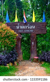 Krabi, Thailand - October 23, 2014: Wooden information sign with flags at the entrance of Hot Stream, or Namtok Ron Hot Spring Waterfall.