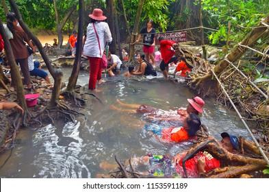 Krabi, Thailand - October 23, 2014: Asian people enjoying a bath at Namtok Ron Hot Spring Waterfall, a natural hot tub.