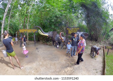 Krabi, Thailand - October 23, 2014: Visitors in front of elephant statues and an information sign for Sa Morakot, or Emerald Pool.
