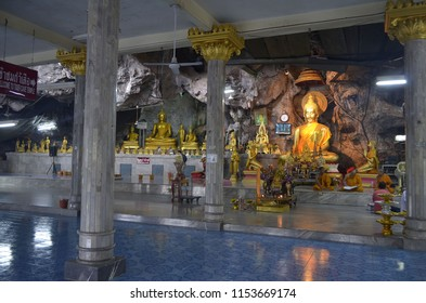 Krabi, Thailand, October 23, 2014: Monks and worshippers inside the cave of the Wat Tham Sua.