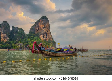 Krabi, Thaliand - April 4, 2018 : Traditional thai longtail boats parked at the Railay Beach just before sunset, with massive cliffs in the background.